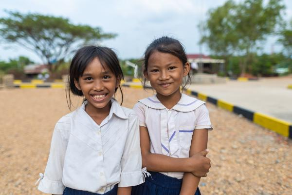 Girls in Cambodia smile at school.