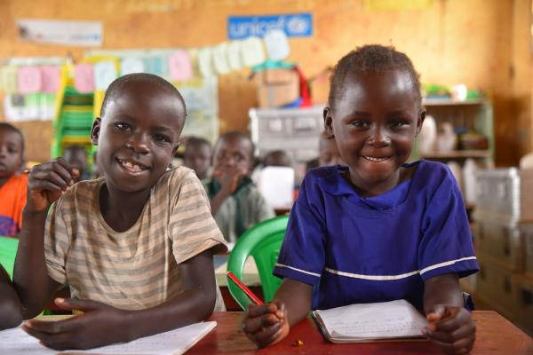 Two children in Uganda sit at a desk.