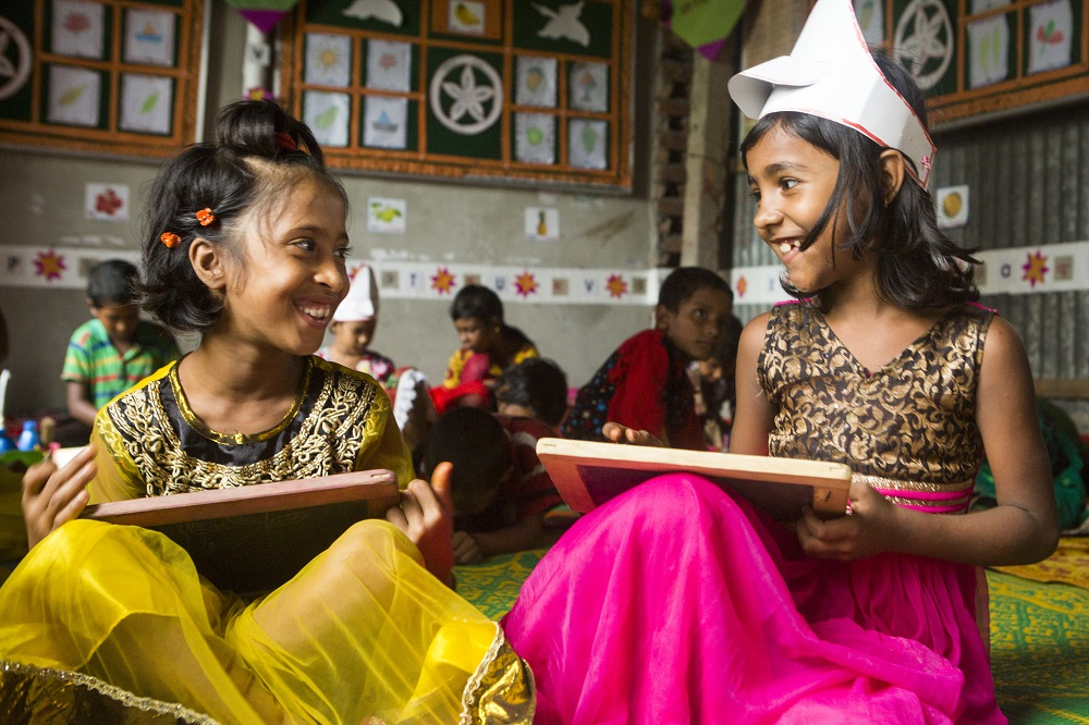 Two girls in Bangladesh paint together in the classroom.