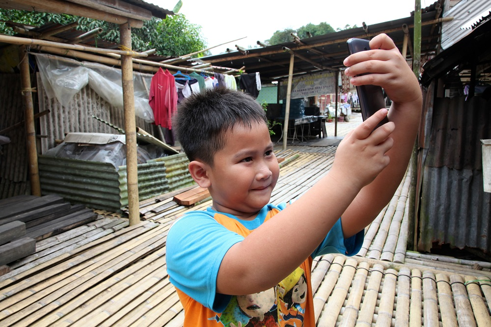 A child in Malaysia uses a smartphone.