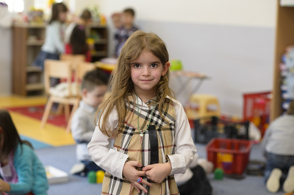 A child in Montenegro stands in a classroom.