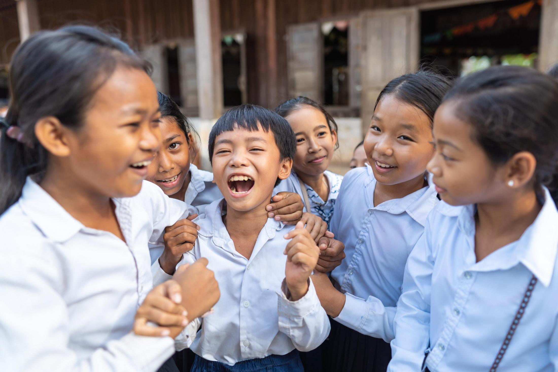 Children laugh outside a school in Cambodia.