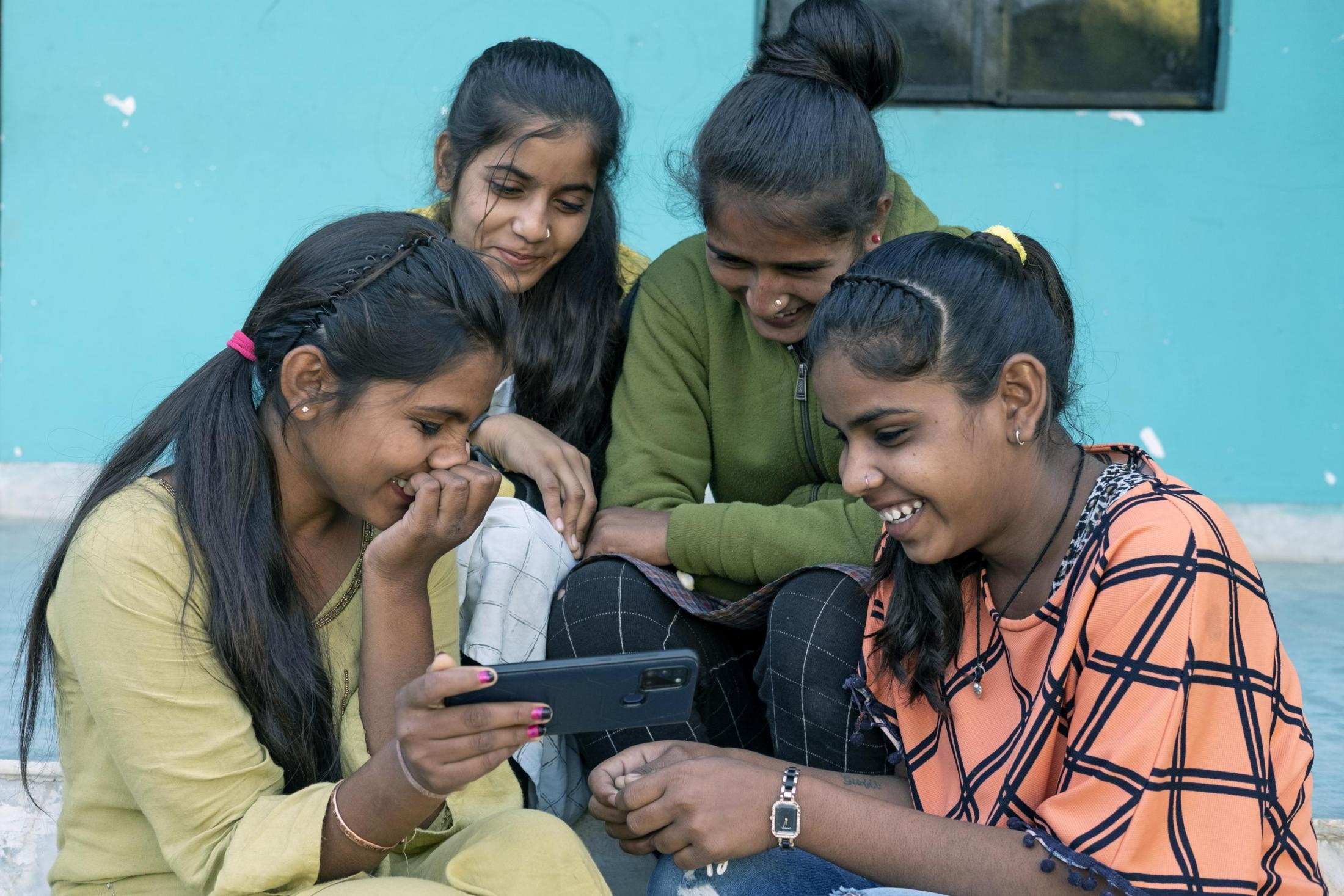 Girls in India laugh over a tablet.