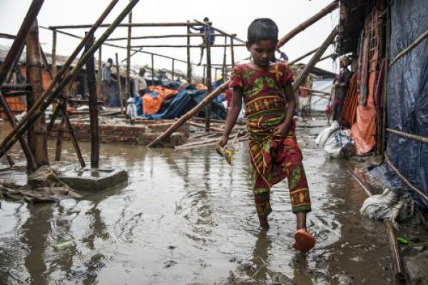 A child in Bangladesh steps through a flood.